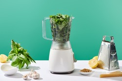 pesto sauce raw ingredients and food processor with basil leaves on white table isolated on green