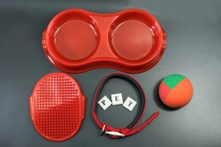 Pet accessories of red concept : bowl, ball and collars on black background.