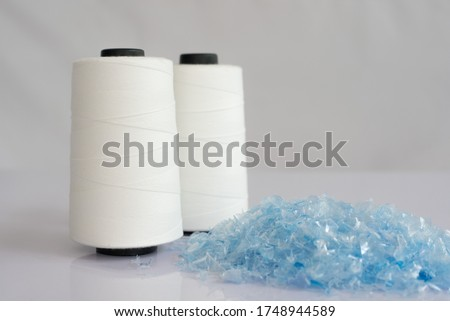 PET bottle flake or Plastic bottle crushed & Raw White Polyester FDY Yarn spool with white background
