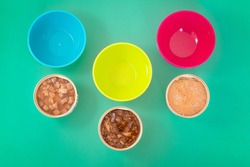 Pet nutrition concept. Cans of wet food for cats. Comparison between different types of tins of food for animals. Cubes, mousse, patè and fine flakes for kitten. Preservatives and scraps theme.