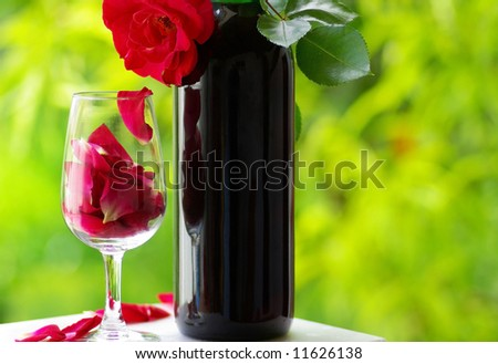 Petals of rose in a  glass of red wine.