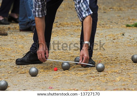 Petanque game in France, measuring the distance, deciding who's the winner