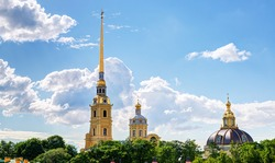 Peter and Paul Cathedral in Saint Petersburg, Russia. It is one of the main landmarks of the city. Golden tall spire of Peter and Paul Cathedral on the blue sky background in summer.