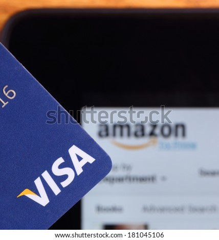PETERSBURG, ILLINOIS-MARCH 8, 2014:  Closeup of a Visa credit card with a tablet showing Amazon's web site in background. Visa, Inc. is an American financial services corporation.