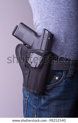 Petite woman carrying holstered gun