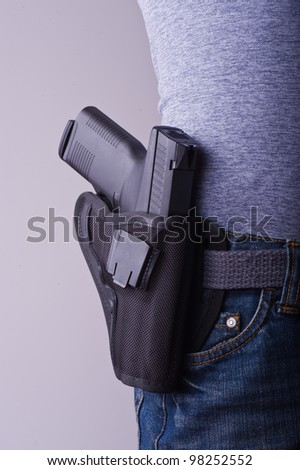 Petite woman carrying holstered gun