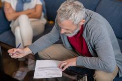 Petition for divorce. An elderly man filling a petition for divorce