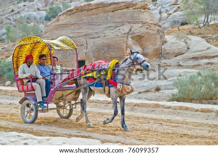 PETRA, JORDAN - NOV 24:  Unidentified Bedouin carriage driver and passengers on November 24, 2010 on way to ancient Petra, Jordan.  Petra is a UNESCO World Heritage Site since 1985.