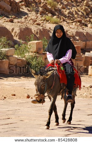 PETRA, JORDAN - NOVEMBER 25: Unidentified Bedouin woman rides through the ruins of ancient Petra on November 25, 2009 in Petra, Jordan. Petra is a UNESCO World Heritage Site since 1985.