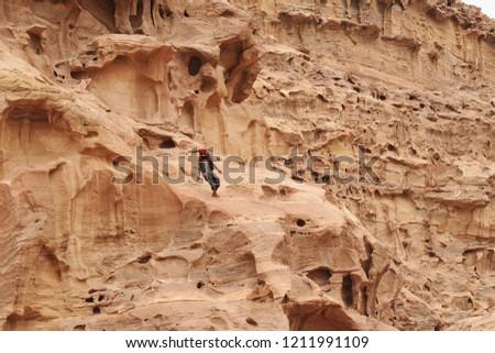 Petra, Jordan - October 1st, 2018: a young bedouin climbing the rocks of the lost town of petra, in jordan