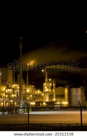 Petro Chemical Refinery Behind Fence at Night