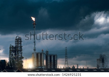 Petrochemical plant and fire on flare stack while burning toxic  oil and gas with cloudy background. #1426925231