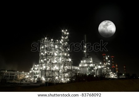 Petrochemical refinery at night with full moon.