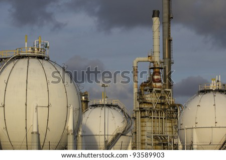 Petrochemical-tanks and a large oil-refinery-plant in the background.