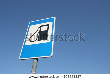 Petrol filling station sign over blue sky.