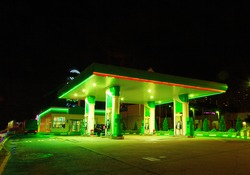 Petrol gas station station at night with lights on and mini-mart