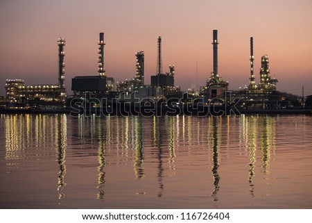 Petroleum oil refinery beside the river at twilight - stock photo