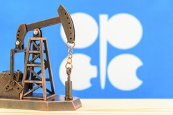 Petroleum, petrodollar and crude oil concept : Pump jack and flag of OPEC or Organization of Oil Exporting Countries, depicts the investment in the development or production of global oil industry.