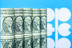 Petroleum, petrodollar and crude oil concept : US USD dollar banknotes, flag of OPEC, depicts the money received or earned from sales after investment in the development or production of oil industry.