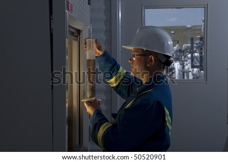 Petroleum worker measures a liquid in a graduated cylinder. He is wearing goggles and a hardhat. Horizontal shot.