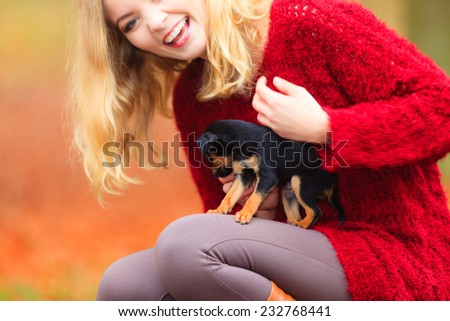 Pets and people, pet adoption. Woman playing with her little dog pet outdoor, hugging lovingly embraces her puppy.