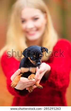 Pets and people, pet adoption. Woman showing her little dog pet outdoor, hugging lovingly embraces her puppy.