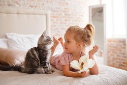 Pets, morning, comfort, rest and people concept - happy little girl with cat in bed at home