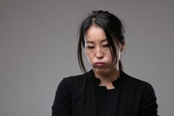 Petulant sulky Asian woman pouting her lips and looking down with a morose expression over a grey studio background with copyspace