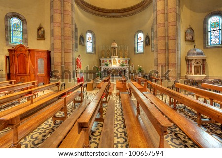 Pews and altar among columns in Madonna Moretta catholic church in Alba, Northern Italy.