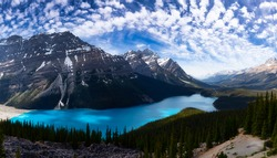 Peyto Lake viewed from the top of a mountain during a vibrant sunny day. Blue Cloudy Sky Art Render. Taken in Icefields Parkway, Banff National Park, Alberta, Canada.