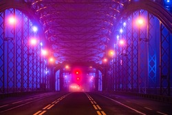 Phantasmagoria. The road is surrounded by metal fences. The lantern-lit deserted road with prohibiting signals. View of a deserted road bridge in the dark. A lighted bridge without people or cars.