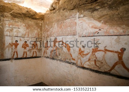 Pharaonic wall paintings on the wall of one of the old tombs next to the pyramids