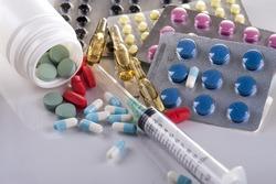Pharmaceutical drugs, syringe and capsules on white background.