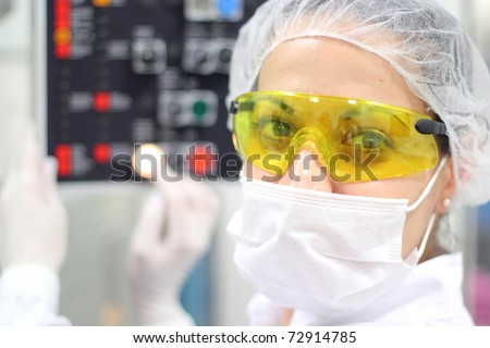 Pharmaceutical Factory Worker. Worker Using Control Panel. A female technician is monitoring the process of pill packaging.