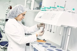 Pharmaceutical scientific  female researcher in protective uniform working with dissolution tester at pharmacy industry manufacture factory laboratory