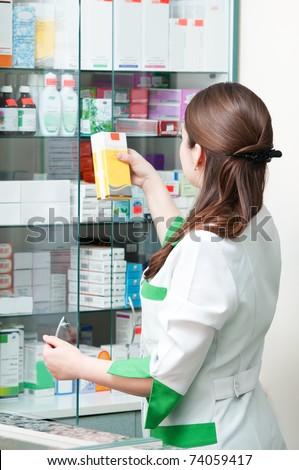 pharmacist chemist woman standing and choosing in pharmacy drugstore