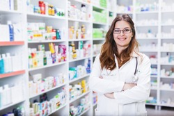 Pharmacist chemist woman standing in pharmacy - drugstore