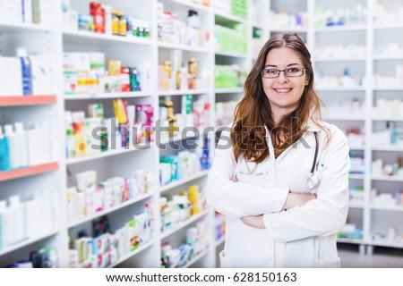 Pharmacist chemist woman standing in pharmacy - drugstore