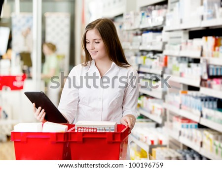Pharmacist filling prescriptions looking at digital tablet