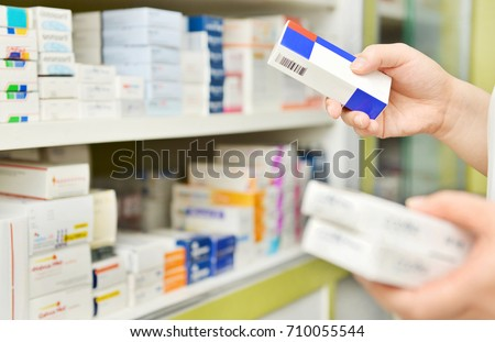 Pharmacist holding medicine box in pharmacy drugstore.