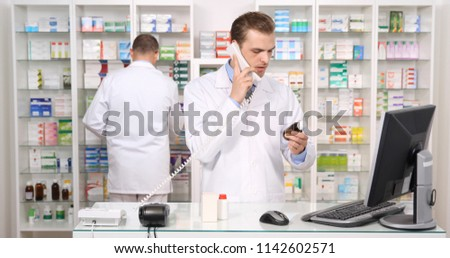 Pharmacist Male Talking on Landline Telephone with Distribution Company while his Colleague Make Inventory in Pharmacy Shop or Drugstore Interior, Pharmaceutical Store Concept