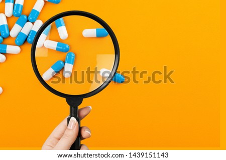 Pharmacist or expert on pharmaceutical inspection identifies pills. Testing, verification and determining pharmaceutical counterfeiting or fakes of medicines and medicinal substance quality concept