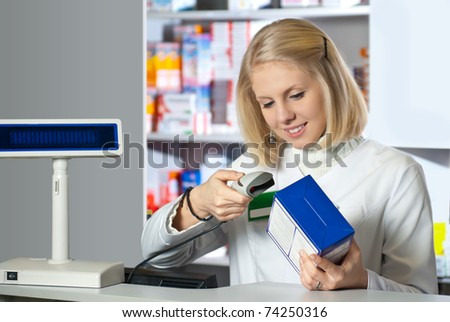 Pharmacist scanning medicine with barcode reader - stock photo