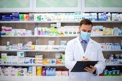 Pharmacist selling medicines in pharmacy shop during corona virus pandemic. Healthcare and medicine.