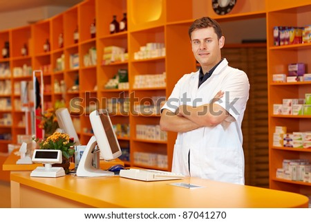 Pharmacist standing with arms crossed in a pharmacy