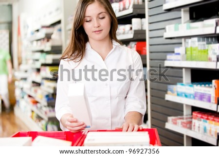 Pharmacist stocking shelves in pharmacy with box of medicine - stock photo