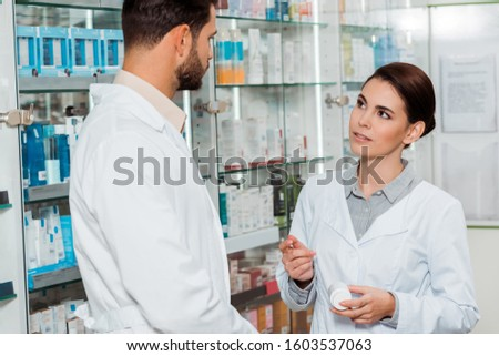 Pharmacist with jar of pills looking at colleague in pharmacy