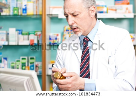 Pharmacist writing on a pill bottle