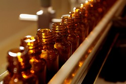 Pharmacological production. Sterile bottles and ampoules on the dispensing line. Sealed ampoules with medicine. Sterile capsules for injection Bottles on the bottling line of the pharmaceutical plant