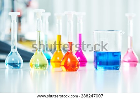 Pharmacy and chemistry theme. Test glass flask with solution in research laboratory. Shallow DOF. Focus on red bottle.